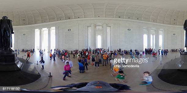 Visitors take photographs of the statue of Thomas Jefferson inside the memorial named for the author of the Declaration of Independence on the Tidal...