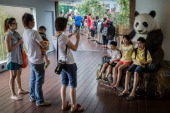 Visitors take photographs with a Giant Panda replica during a media tour ahead of the opening of River Safari at the Singapore Zoo on March 25 2013...