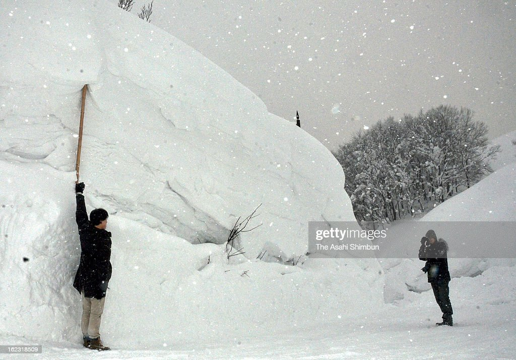 Visitors take photographs with the snow wall at Sukayu hot spring area on February 21, 2013 in Aomori, Japan. 515 centimeters of snow fall is observed at 1 p.m, breaks the former record of 502 centimeters in 1979.