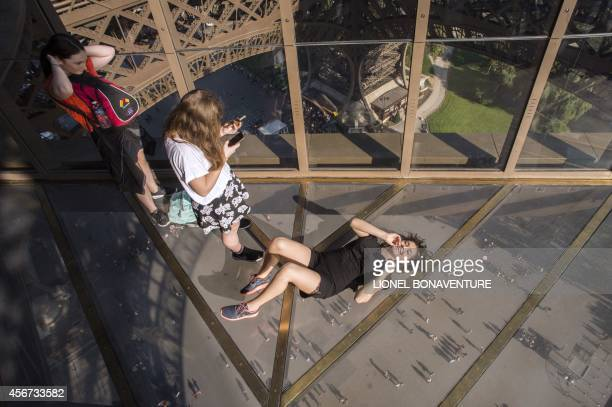 Visitors take photos as they lie down on the new glass floor at the Eiffel Tower in Paris on October 3 2014 The Eiffel Tower is inaugurating a new...