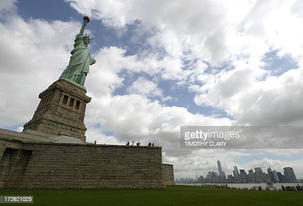 Visitors take photos at the Statue of Liberty as Liberty Island opens to the public on July 4 2013 for the first time since Superstorm Sandy slammed...