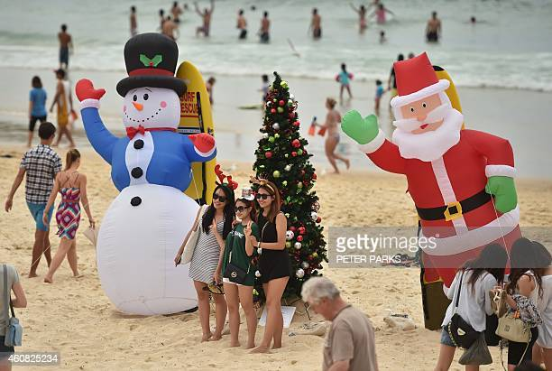 Visitors take photos in front of an inflatable snow man and Santa Claus on Bondi Beach on Christmas Day December 25 2014 Bondi Beach is a popular...
