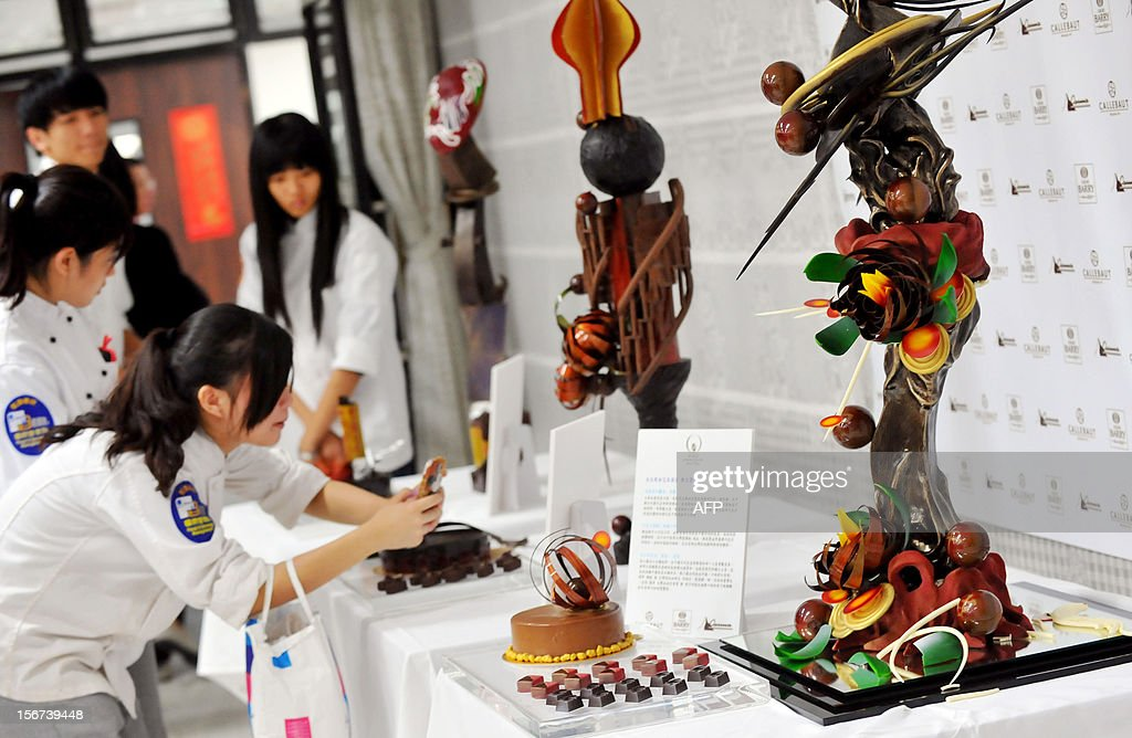 Visitors take photos of chocolate creations during the Taiwan district of 2013 World Chocolate Masters Competition (WCM) in Taipei on November 20, 2012. Chef Chris Cheng won the event and will compete in the Asia-Pacific World Chocolate Masters Competition (WCM) in March 2013. AFP PHOTO / Mandy CHENG
