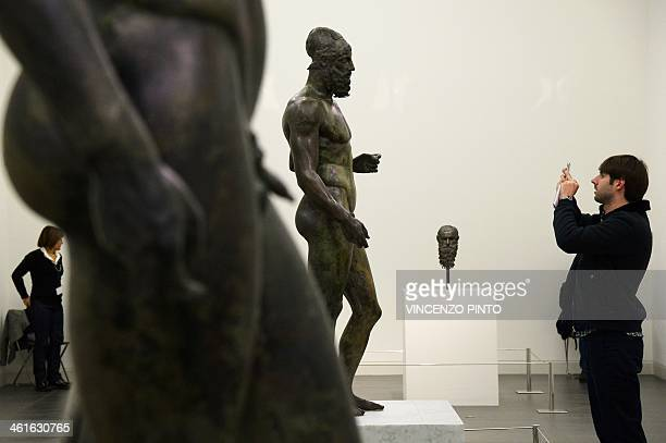 Visitors take photos of the 2500yearold Riace Bronzes that are displaiyed in a renovated Reggio Calabria National Archeological Museum on January 9...