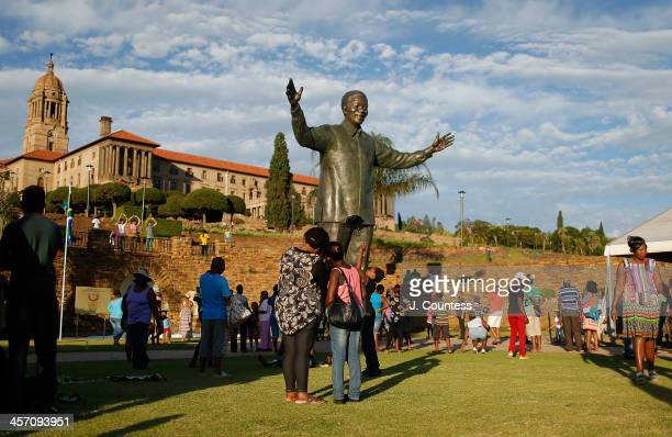 Visitors take photos of the statue of Former South African President Nelson Mandela that was unveiled at the Union Buildings on December 16 2013 in...