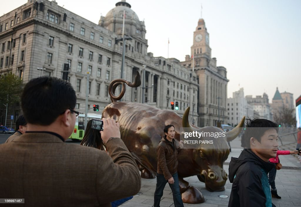 Visitors take photos with a replica of the famous Wall Street bull on the Bund in Shanghai on November 27, 2012. Chinese shares closed at their lowest level in nearly four years on growing pessimism about the domestic economy and the absence of new government moves to support growth, dealers said. AFP PHOTO/Peter PARKS