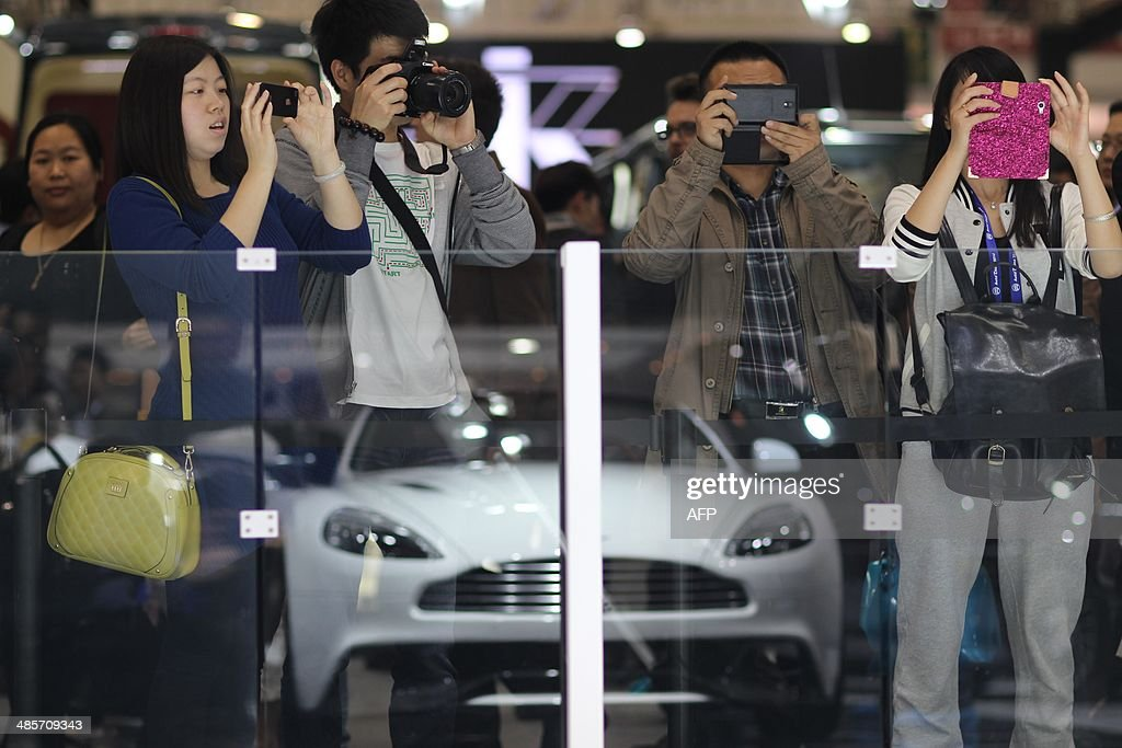 Visitors take pictures of a McLaren car on display at the China International Exhibition Center new venue during the 'Auto China 2014' Beijing International Automotive Exhibition in Beijing on April 20, 2014. Leading automakers are gathering in Beijing for the kickoff of China's biggest car show, but lackluster growth and environmental restrictions in the world's largest car market have thrown uncertainty into the mix. More than 1,100 vehicles are being showcased at the auto show, which opens to the public on April 21. CHINA