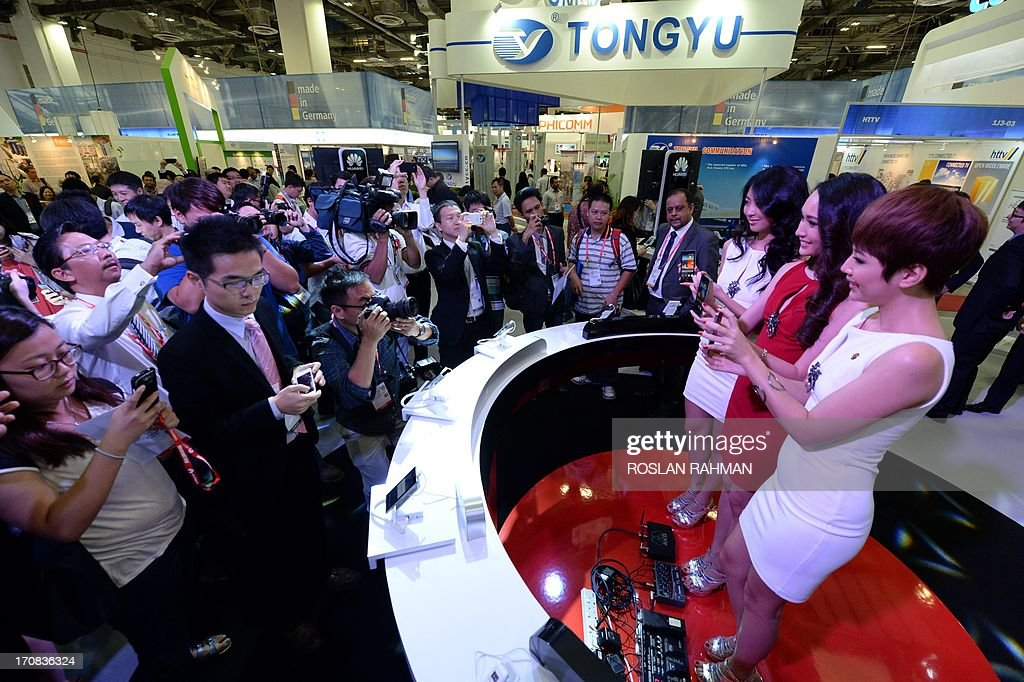 Visitors take pictures of promoters displaying Huawei's Ascend P6 phone billed as the world's thinnest smartphone at the CommunicAsia telecom and...