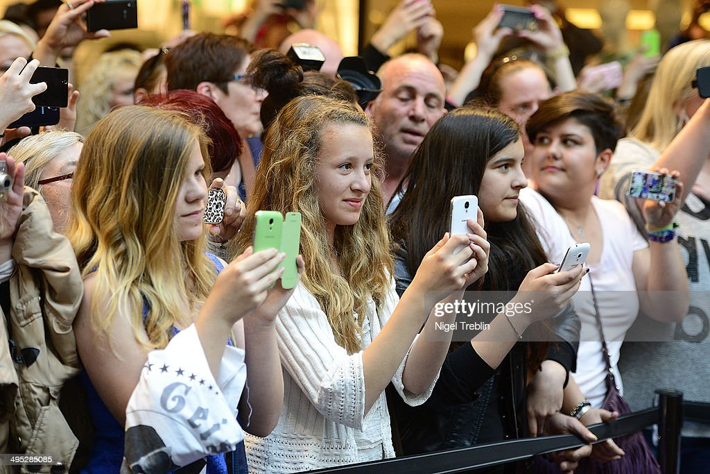 Visitors take pictures of Robert and Carmen Geiss during the opening event of a new Titan Shop on June 2, 2014 in Osnabruck, Germany.