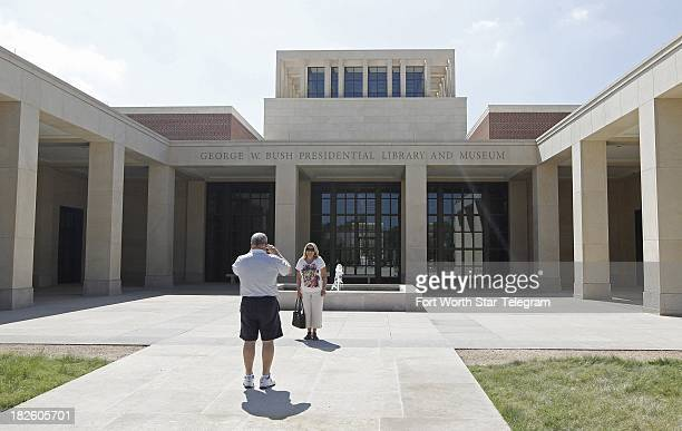 Visitors take pictures outside the George W Bush Presidential Library and Museum in Dallas Texas Tuesday Oct 1 2013 The facility was closed due to...