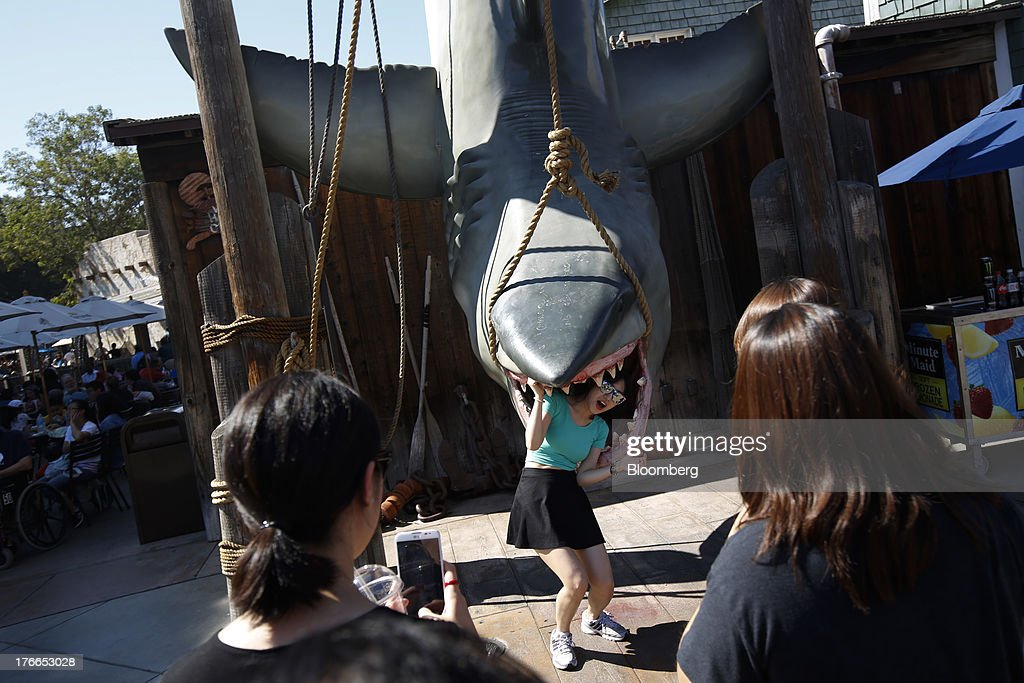 Visitors take pictures with a statue of 'Jaws' at the Universal Studios Hollywood theme park in Hollywood, California, U.S., on Thursday, Aug. 15, 2013. NBC Universal, majority owned by Comcast Corp., operates some of the most-watched U.S. cable TV channels, in addition to its flagship broadcast network, a film studio and the Universal Studios amusement parks. Photographer: Patrick T. Fallon/Bloomberg via Getty Images