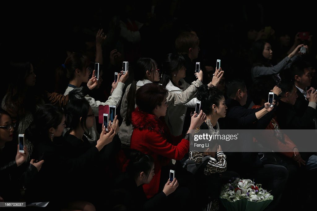 Visitors take pictures with smart phones as Chinese actress Liu Yuxin showcases designs on the runway at DEVEN Wedding Dress Collection show during Mercedes-Benz China Fashion Week Spring/Summer 2014 at 751 D-PARK Workshop on October 27, 2013 in Beijing, China.
