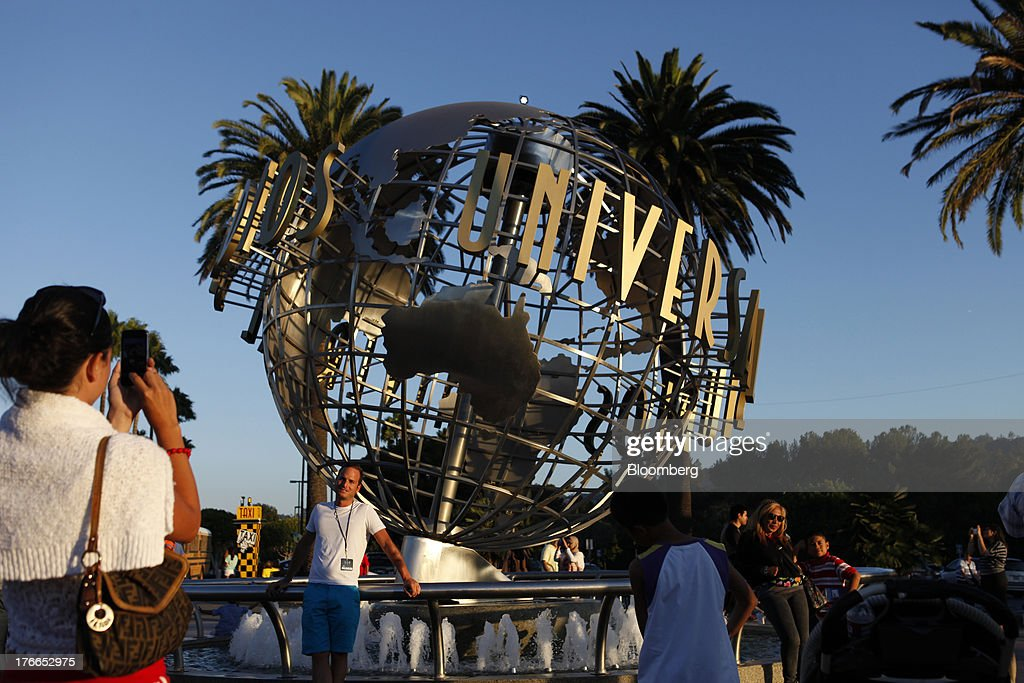 Visitors take pictures with the Universal globe at the main entrance to the Universal Studios Hollywood theme park in Hollywood, California, U.S., on Thursday, Aug. 15, 2013. NBC Universal, majority owned by Comcast Corp., operates some of the most-watched U.S. cable TV channels, in addition to its flagship broadcast network, a film studio and the Universal Studios amusement parks. Photographer: Patrick T. Fallon/Bloomberg via Getty Images