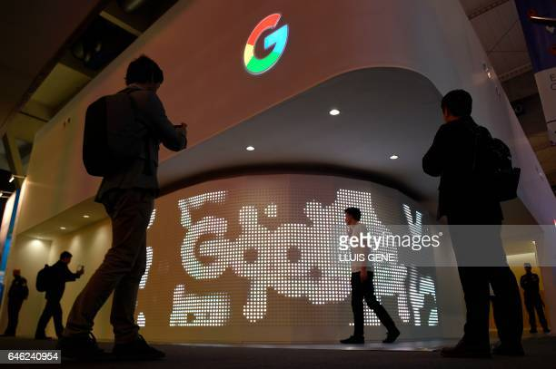 Visitors take pictures with their mobile phones at the stand of Google on the second day of the Mobile World Congress on February 28 2017 in...