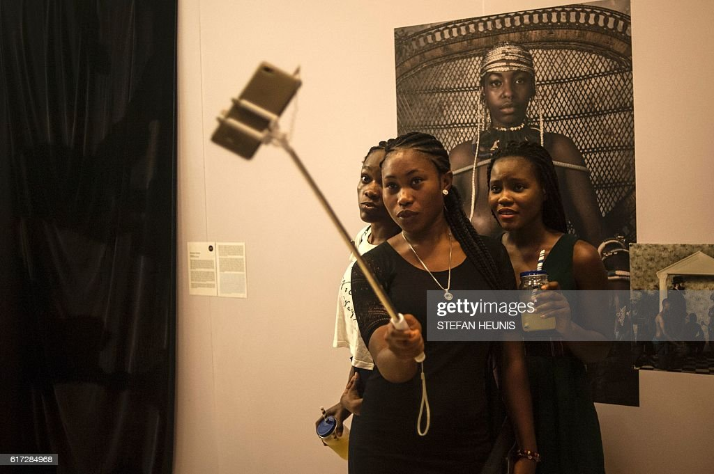 Visitors take selfies during the opening of the Lagos Photo festival in Lagos on October 22, 2016. Lagos Photo was launched in 2010 and is the first and only international arts festival of photography in Nigeria. / AFP / STEFAN