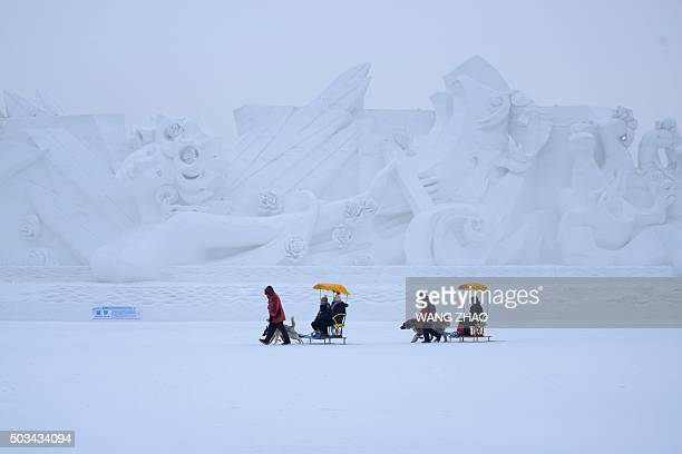 Visitors take sleighs past snow sculptures during the Harbin International Ice and Snow Festival in Harbin northeast China's Heilongjiang province on...