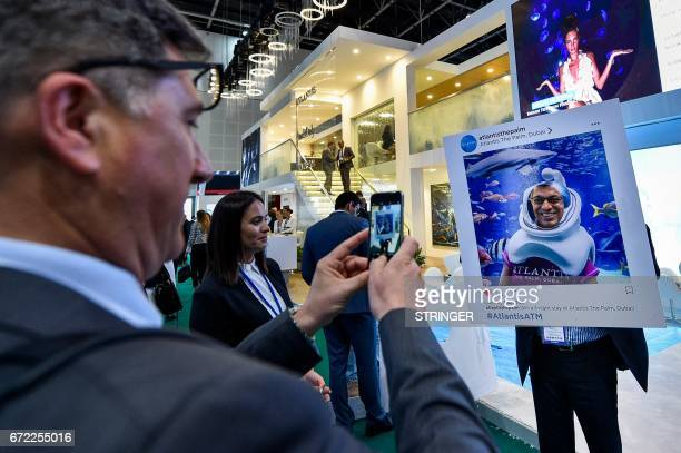 A visitors takes a photo at the Atlantis pavilion during the Arabian Travel Market 2017 at the Dubai World Trade Centre on April 24 2017 / AFP PHOTO...