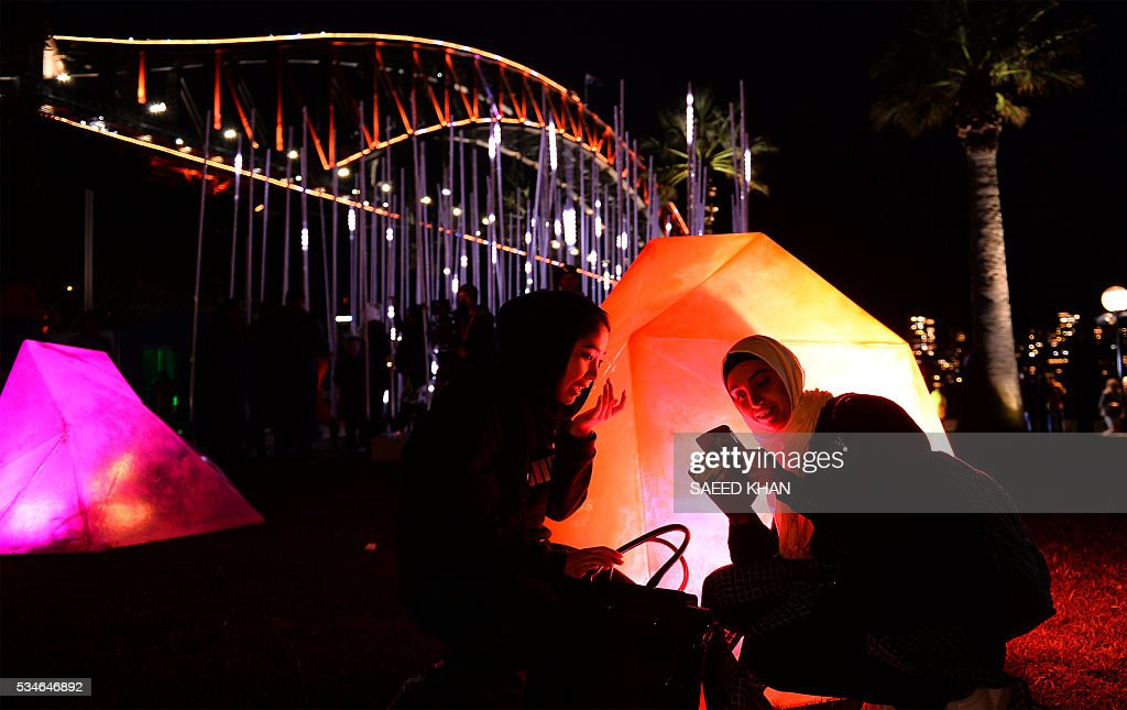 Visitors takes pictures under Australia's iconic Harbour Bridge on the opening night of Vivid Sydney on May 27, 2016. Vivid Sydney, an annual festival of light, music and ideas, runs from May 27 to June 18. / AFP / SAEED