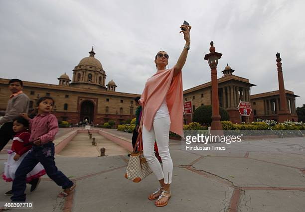 Visitors taking 'selfie' at North block during cloudy weather on March 15 2015 in New Delhi India The maximum temperature recorded on Saturday was...