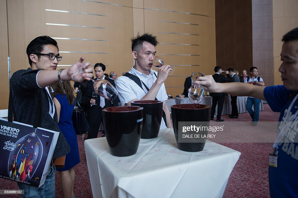 Visitors taste wine during Vinexpo in Hong Kong on May 24, 2016. The international wine and spirits exhibition runs from May 24 to 26. / AFP / DALE