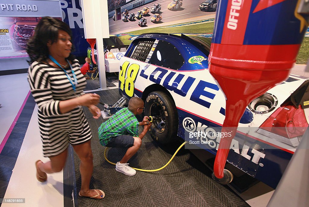 Visitors test their pit stop skills at the NASCAR Hall of Fame on July 11, 2012 in Charlotte, North Carolina. The HOF features cars, driver memorabilia and interactive experiences. Businesses and attractions in Charlotte are anticipating a boost in visitors when the city hosts the 2012 Democratic National Convention (DNC) September 3-6.