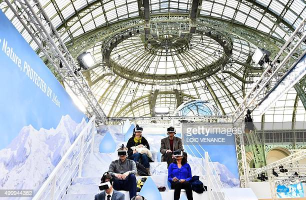 Visitors test virtual reality headsets at the 'Solutions COP21' exhibition at the Grand Palais in Paris on December 4 2015 on the sidelines of the...