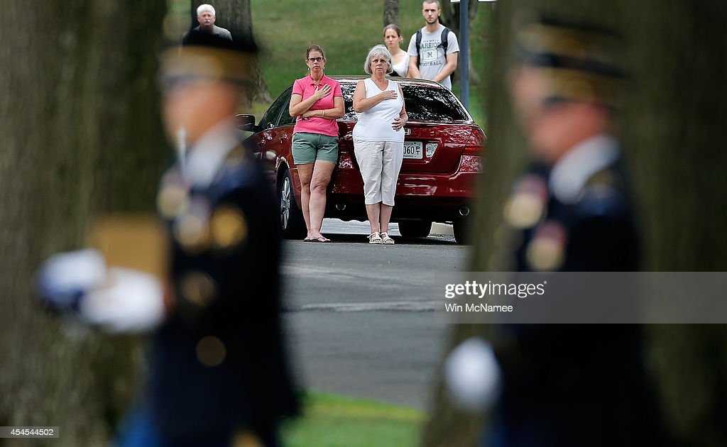 Visitors to Arlington National Cemetery place their hands over their hearts as they view the start of a burial service for Sgt. First Class Matthew Leggett September 3, 2014 in Arlington, Virginia. Leggett, a paratrooper stationed at Ft. Bragg who received the Bronze Star Medal and Purple Heart, was killed in action on August 20, 2014 while serving his third tour of Afghanistan.