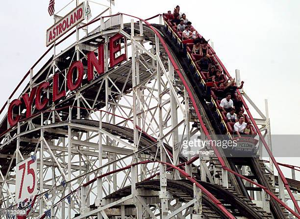 Visitors to Coney Island enjoy a thrill ride on the world famous 'Cyclone' rollercoaster July 14 2002 in Coney Island New York Coney Island...
