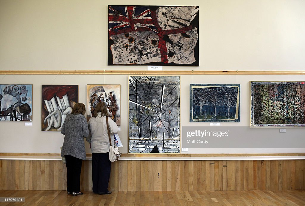 Visitors to Exeter Castle look at paintings including (top) Battle Ensign by ex-Royal Navy gunner, John Mc Dermott on June 21, 2011 in Exeter, England. The paintings are among artworks produced by former and current servicemen and women currently being exhibited at Exeter Castle. The free exhibition, Entrance to War Art, aims to foster understanding between Post Traumatic Stress Disorder (PTSD) sufferers and the wider community and runs until Sunday.
