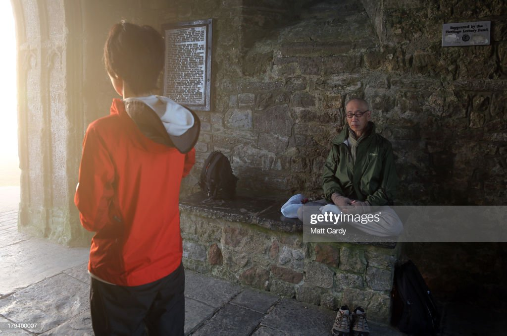 Visitors to Glastonbury Tor meditate inside St. Michael's Tower, a ruined 14th-century church tower, as the rising sun begins to clear the early morning mist and fog near the town of Glastonbury on September 4, 2013 in Somerset, England. Parts of the UK are set to enjoy a late summer heatwave today, with temperatures possibly reaching 28C in central, eastern and southern England, with temperatures predicted to climb even higher tomorrow.