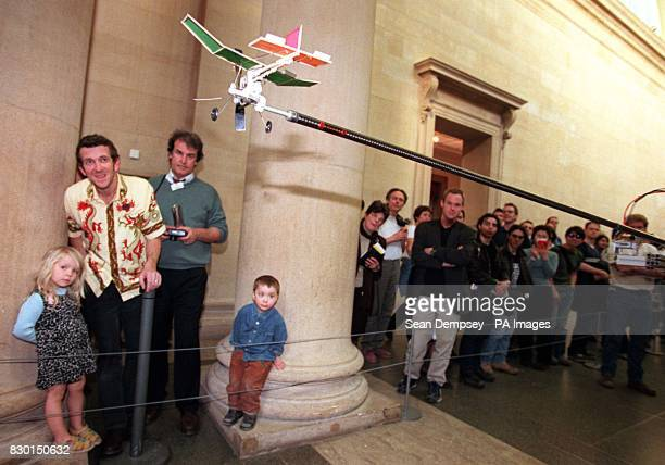 Visitors to London's Tate Gallery watch the launch of a model plane from a machine produced by American artist Chris Burden His device is an assembly...