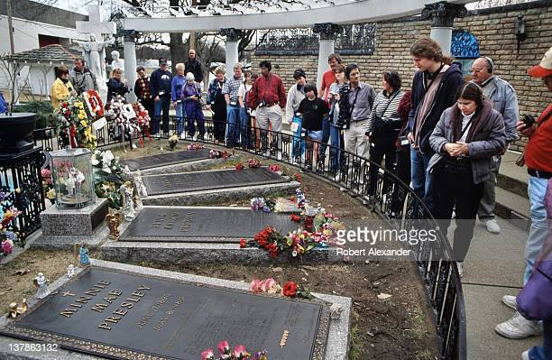 Visitors to singer Elvis Presley's 'Graceland' estate in Memphis Tennessee pause at the late singer's grave Buried beside Presley are his parents and...