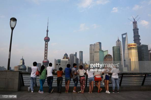 Visitors to the Bund area look at buildings in the Lujiazui district of Shanghai China on Sunday June 30 2013 China's President Xi Jinping said...