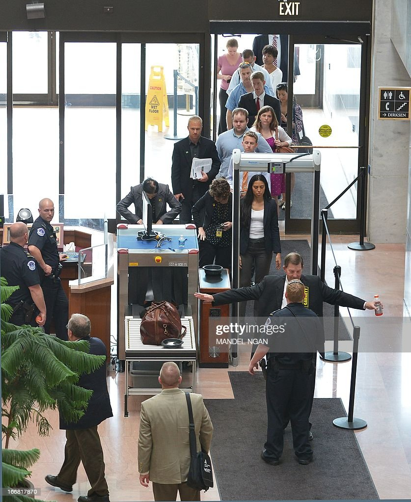 Visitors to the Hart Senate Office Building wait in line to pass through a security check after the building was re-opened on April 17, 2013 on Capitol Hill in Washington, DC. The building was closed earlier following reports of a suspicious package. AFP PHOTO/Mandel NGAN