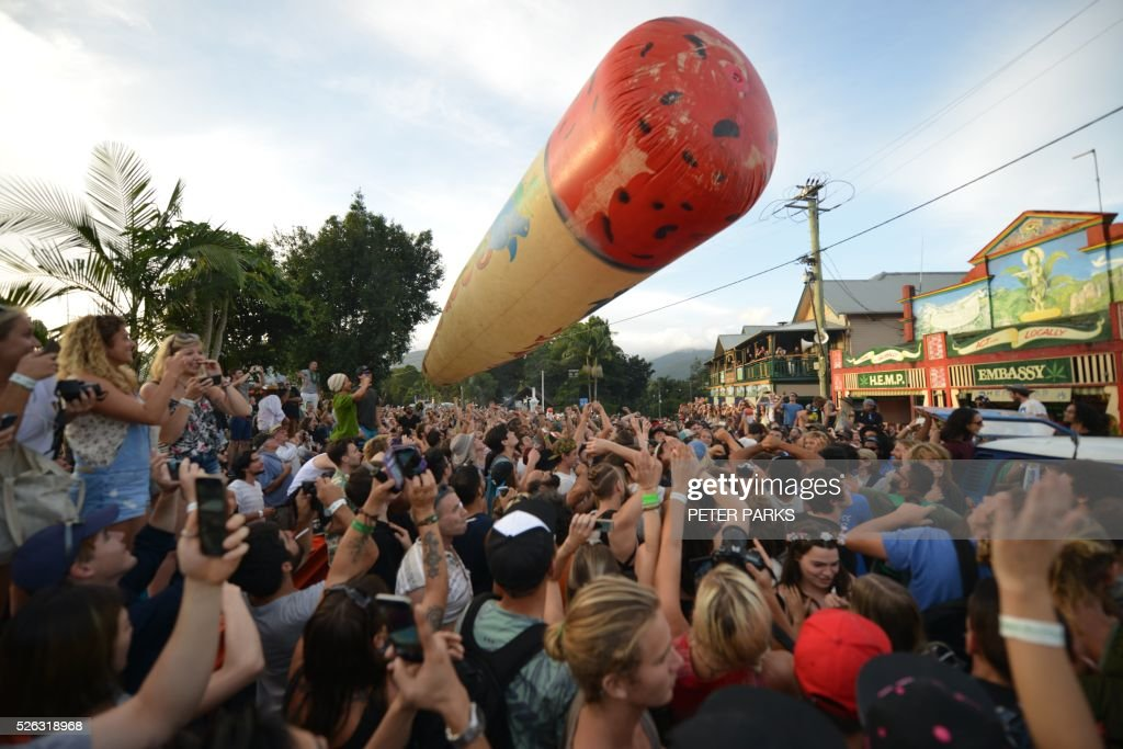 Visitors to the Mardi Grass festival push up a giant inflatable joint above their heads as part of the Global Marijuana March in the eastern Australian town of Nimbin on April 30, 2015. The festival, an annual cannabis law reform protest and gathering, attracts thousands of revellers from across Australia and around the world. / AFP / PETER