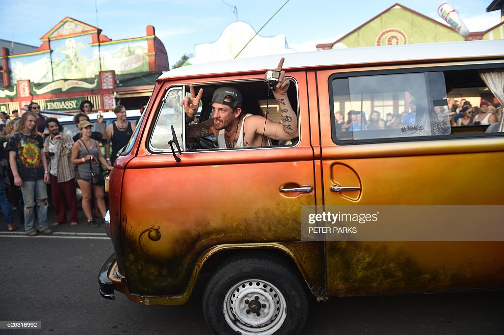Visitors to the Mardi Grass festival take part in the 'Kombi Konvoy' as part of the Global Marijuana March in the eastern Australian town of Nimbin on April 30, 2016. The festival, an annual cannabis law reform protest and gathering, attracts thousands of revellers from across Australia and around the world. / AFP / PETER