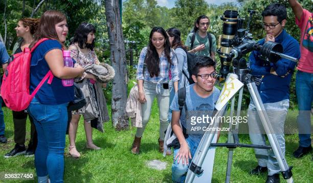 Visitors to the National Autonomous University of Mexico Institute of Astronomy take turns watching the solar eclipse through a telescope installed...