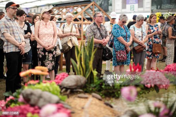Visitors to the RHS Chelsea Flower Show pause to observe a minute silence for the victims of the Manchester Arena terror attack on May 25 2017 in...