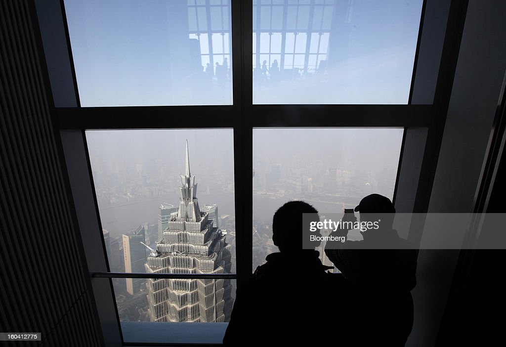 Visitors to the Shanghai World Financial Center look at the Jin Mao Tower, center left, in the Pudong area of Shanghai, China, on Wednesday, Jan. 30, 2013. China's economic growth accelerated for the first time in two years as government efforts to revive demand drove a rebound in industrial output, retail sales and the housing market. Photographer: Tomohiro Ohsumi/Bloomberg via Getty Images