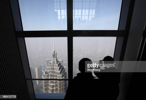 Visitors to the Shanghai World Financial Center look at the Jin Mao Tower center left in the Pudong area of Shanghai China on Wednesday Jan 30 2013...