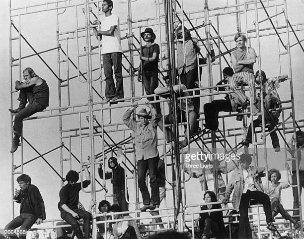 Visitors to the Woodstock pop festival in New York State climbing the sound tower to secure a better viewing point