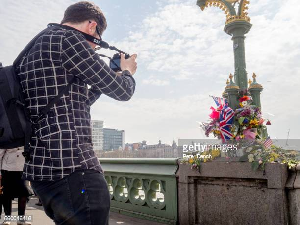 A visitors to Westminster Bridge in London photographs a floral tribute have left for victims of the terror attack in Westminster on the 22nd March...