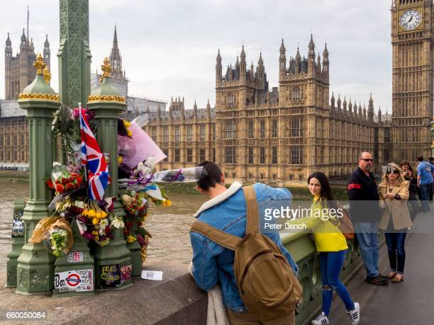 Visitors to Westminster Bridge in London take photographs next to where a floral tribute has been left for victims of the terror attack in...