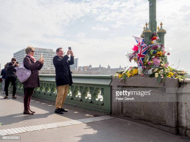 Visitors to Westminster Bridge in London where floral tributes have been left for victims of the terror attack in Westminster on the 22nd March...