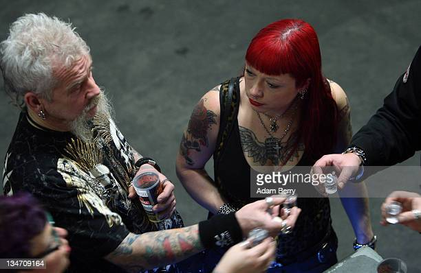 Visitors toast with shots of vodka at the 21st International Tattoo Convention Berlin on December 3 2011 in Berlin Germany The annual tattoo trade...