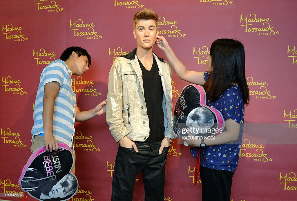 Visitors touch a life-size wax figure of Canadian pop musician Justin Bieber at Tokyo's Madame Tussaud wax museum on September 5, 2013. The newest figure of Justin Bieber will be displayed during a limited run exhibition here September 7 to October 20, to commemorate Bieber's visit to Japan for the first time in two years.