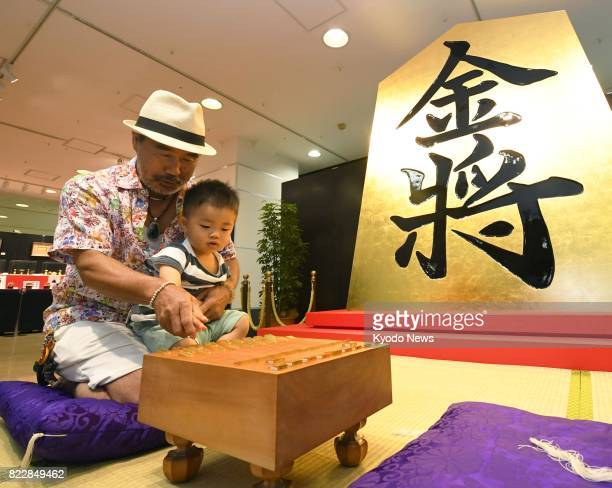 Visitors touch pieces made of pure gold for shogi or Japanese chess in front of a giant piece covered in leaf gold at the Takashimaya department...