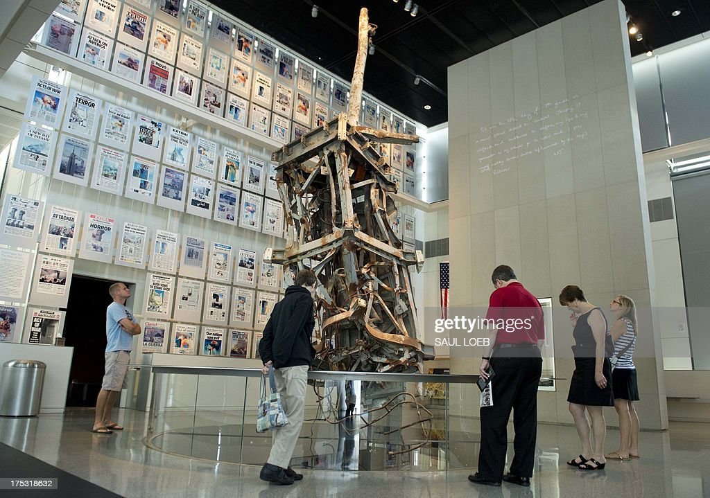 Visitors tour the September 11, 2001 gallery, including a piece of the radio tower from the top of the North Tower of the World Trade Center and front-pages of newspapers from around the world following the terrorist attacks, at the Newseum, a 250,000 square-foot museum dedicated to news, in Washington, DC, on August 2, 2013. AFP PHOTO / Saul LOEB