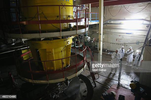 Visitors touring the former Chernobyl nuclear power plant look at one of eight giant cooling water pumps for reactor three on September 29 2015 near...