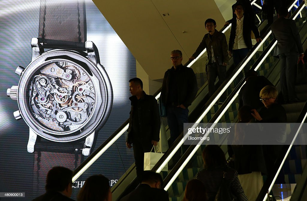 Visitors travel on an escalator as they pass the Patek Philippe SA display booth during the Baselworld luxury watch and jewelry fair in Basel, Switzerland, on Thursday, March 27, 2014. Over 1,400 companies from the watch, jewelry and gem industries will display their latest innovations and products to more than 120,000 visitors at this year's luxury show. Photographer: Gianluca Colla/Bloomberg via Getty Images